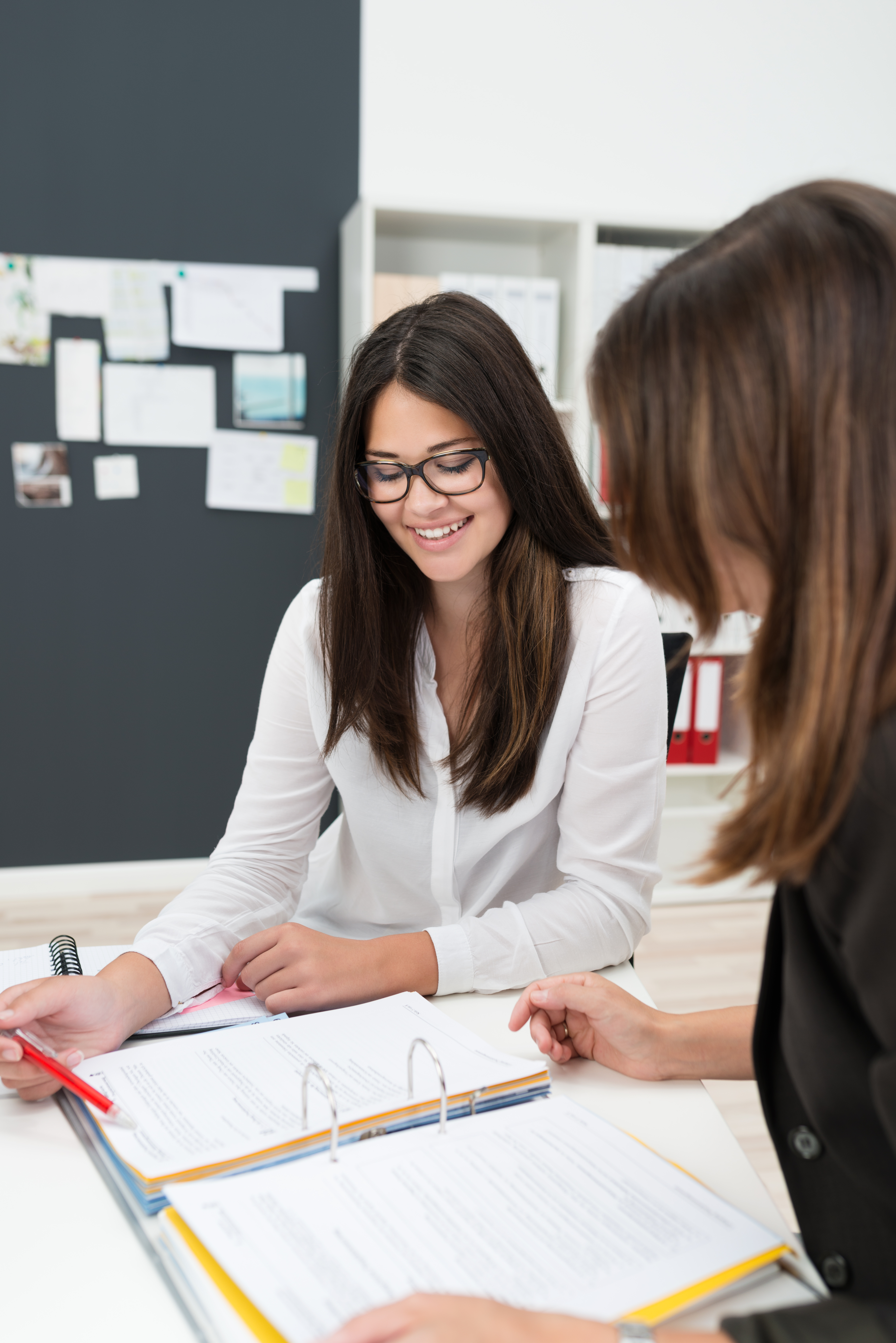 Two Businesswomen Looking at Notes in Meeting