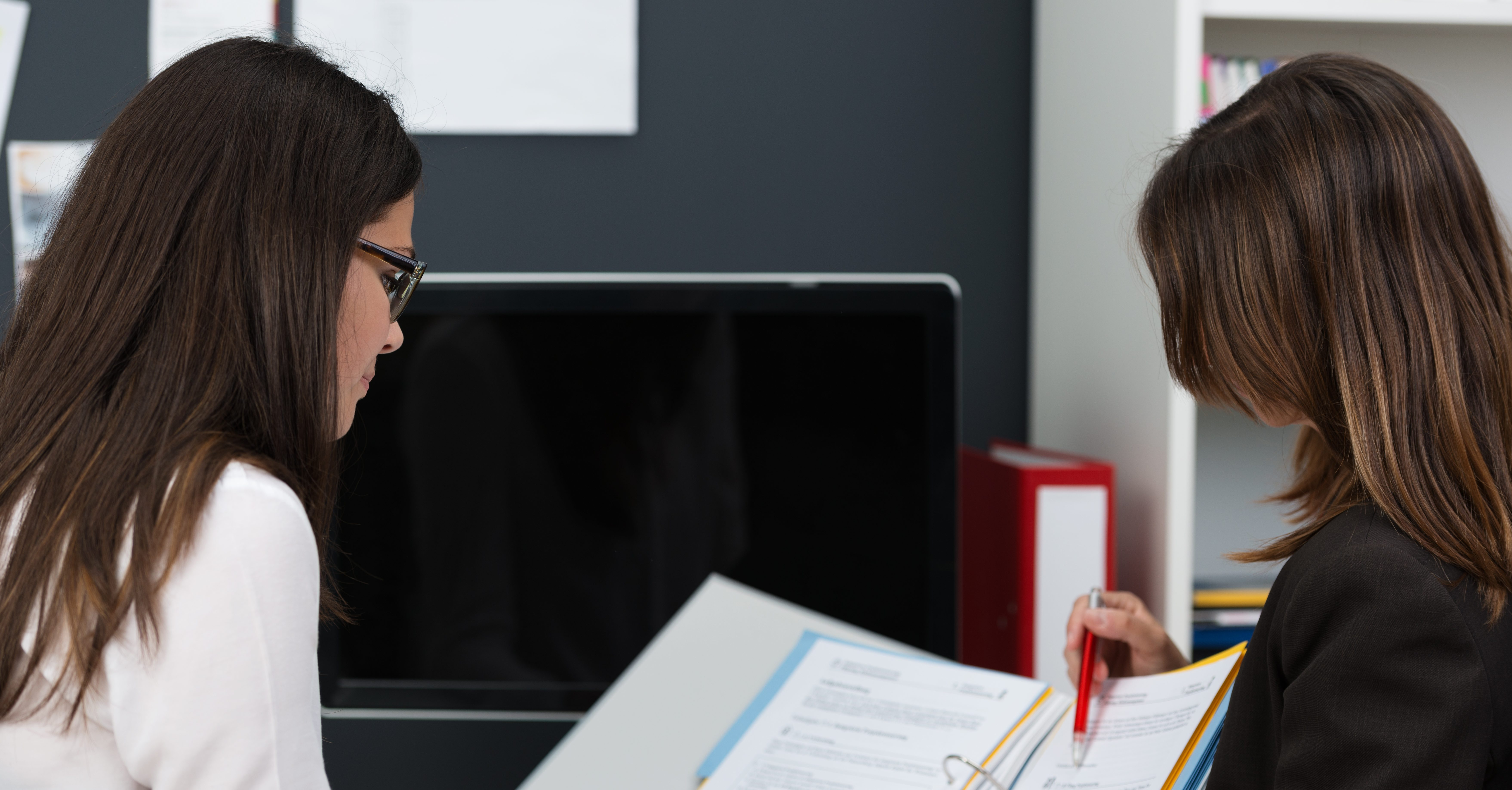 Two young women in the office working on paperwork as they sit together at a desk, over the shoulder view of the file they are working on